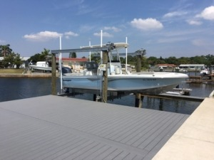 An aluminum boat lift next to a composite stationary dock on the water