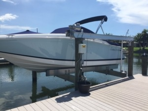 An aluminum direct drive assembly boat lift next to a stationary dock on the water