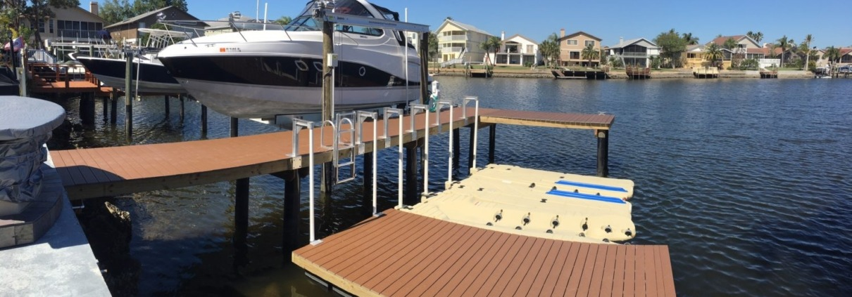 An aluminum direct drive boat lift next to a stationary dock and floating docks